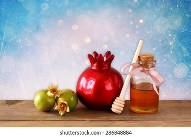 rosh hashanah (jewesh holiday) concept - honey and pomegranate over wooden table. traditional holiday symbols.