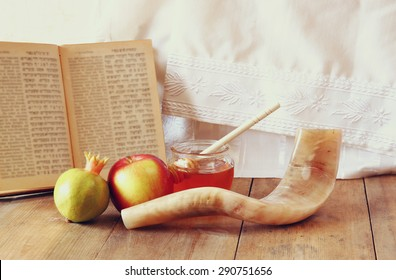 rosh hashanah (jewesh holiday) concept - shofar, torah book, honey, apple and pomegranate over wooden table. traditional holiday symbols.