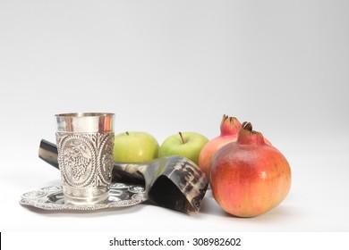 rosh hashanah (jewesh holiday) concept - shofar , Kiddush cup , honey, apple and pomegranate over White background . traditional holiday symbols.