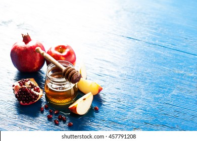 Rosh hashanah (jewesh holiday) concept: honey, apple and pomegranate, with space for text