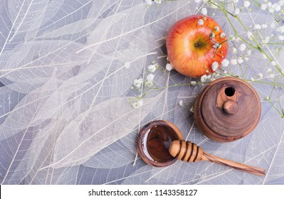 Rosh Hashanah Jewish holiday concept - red yellow apple, wooden dipper on saucer of honey, Honey jar on white leaves background and white flowers. Traditional holiday symbols