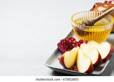 Rosh hashanah (jewish holiday) concept: honey, apple and pomegranate, with copy space