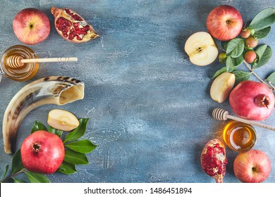 Rosh hashanah - jewish New Year holiday concept. Traditional symbols: Honey jar and fresh apples with pomegranate and shofar -horn on a blue background. Copy space for text. View from above