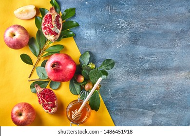 Rosh hashanah - jewish New Year holiday concept. Traditional symbols: Honey jar and fresh apples with pomegranate and shofar -horn on orange-blue background. Copy space for text. View from above