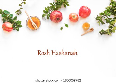 Rosh Hashanah jewish New Year holiday concept banner. Creative layout of traditional symbols - apples, honey, pomegranate isolated on white, top view, copy space.