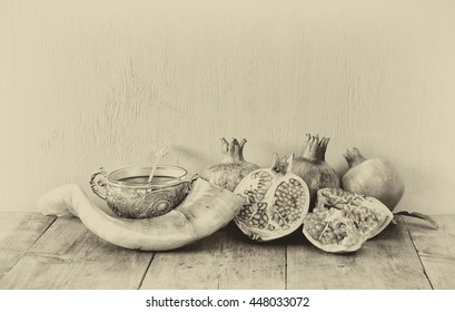 Rosh hashanah (jewish New Year holiday) concept - honey, shofar (horn) and pomegranate over wooden table. Traditional symbols. Sepia style photo