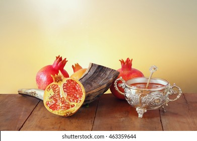 Rosh hashanah (jewish New Year holiday) concept - shofar (horn) and pomegranates over wooden table. Traditional symbols
