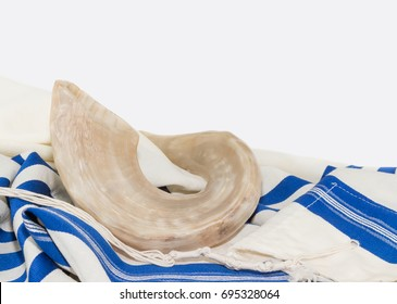 Rosh Hashanah shofar with blue and white striped tallit. Isolated on white background.