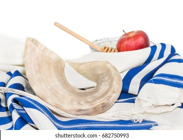 Rosh Hashanah shofar and tallit isolated on white background. Red apple, honey bowl and wooden stick in blurred background. Religious objects for Jewish holiday.
