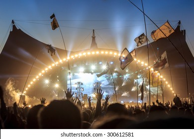 ROSKILDE, DENMARK - JULY 2 Audience with flags and banners, raising their hands in front of the stage at Roskilde Festival 2015. Roskilde Festival is one of the largest music festivals in Europe.