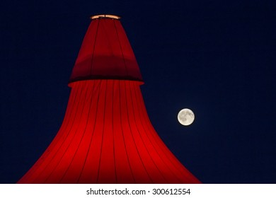 ROSKILDE, DENMARK - JULY 2 Full moon behind glowing stage tent at Roskilde Festival 2015. Roskilde Festival is one of the largest music festivals in Europe.