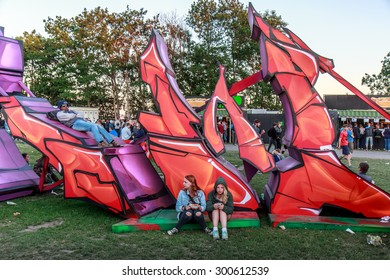 ROSKILDE, DENMARK - JULY 2 Two girls relaxing while texting and eating in front of giant graffiti art at Roskilde Festival 2015. Roskilde Festival is one of the largest music festivals in Europe.