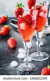 Rossini alcoholic cocktail with Italian sparkling wine, strawberry puree and ice in champagne glasses, place for text, selective focus