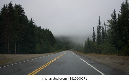 Rossland, British Columbia / Canada - September 26 2020: Mountain highway outside of rossland BC, heading into the mist of a misty mountain range with evergreen alpine forest, overcast grey skies