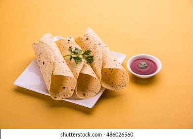 rosted papad or roll papad, indian traditional started food or side dish served with tomato ketchup or sause