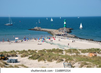 Rostock, Germany - august 03, 2018: View of an area of Warnemunde beach, with people sunbathing and sailboats sailing in the sea