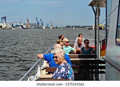 Rostock, Germany - Circa 2018: A group of tourists enjoying a boat tour in the Warnemunde harbor.