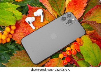 ROSTOV, RUSSIA - August 26, 2020: new Apple iPhone 11 or 12 Pro Wireless headphones AirPods Pro lie on colorful foliage. Autumn presentation or event Apple. The latest model of mobile phones.