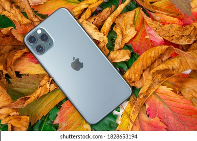 ROSTOV, RUSSIA - August 26, 2020: top view new Apple iPhone 11 or 12 Pro lie on colorful foliage. Autumn presentation or event Apple The latest model of mobile phones. Modern technologies.