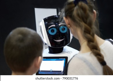 """Rostov, Russia - December 28: Children boy and girl talking, playing with an android robot at the exhibition """"City of Robots"""" December 28, 2017 in Rostov, Russia."""