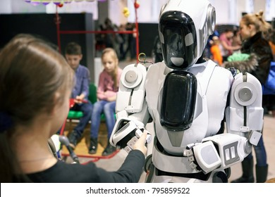 """Rostov, Russia - December 28: The girl stretches out her hand to the robot as a sign of friendship and understanding at the exhibition """"City of Robots"""" in Rostov, December 28, 2017."""