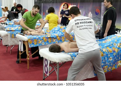 """Rostov, Russia - February 10, 2018: Training of massage masseurs for children's massage at the """"School of masseurs"""" stand at the """"Sharm"""" exhibition in Rostov."""