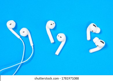Rostov, Russia - July 06, 2020:  Comparison of three generations of headsets for smartphones Apple wired headphone, wireless AirPods and new AirPods Pro on blue background, top view, copy space.