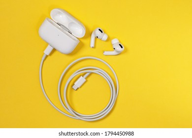 Rostov, Russia - July 06, 2020: Wireless Apple headphones AirPods Pro with soft, flexible silicone tapered tips conforming human ear shape in charging case connected to cord, top view, copy space