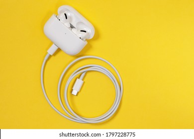 Rostov, Russia - July 06, 2020: Wireless Apple headphones AirPods Pro with soft, flexible silicone tapered tips conforming human ear shape in charging case connected to cord, top view, copy space.