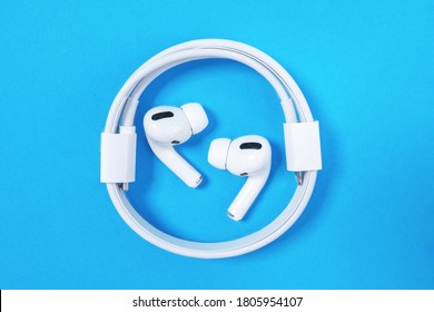Rostov, Russia - July 06, 2020: Wireless headphones Apple AirPods Pro with soft, flexible silicone tapered tips conforming human ear shape laying in the ring of coiled charging cord, top view, copy