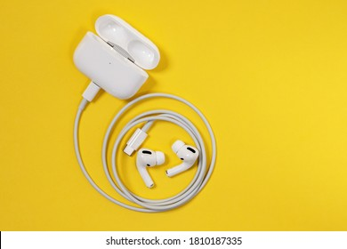 Rostov, Russia - July 06, 2020: Wireless Apple headphones AirPods Pro with soft, flexible silicone tapered tips conforming human ear shape in charging case connected to cord, top view.