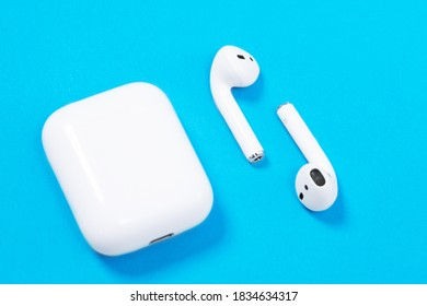 Rostov, Russia - July 06, 2020: Apple AirPods wireless Bluetooth headphones and charging case for Apple iPhone lie on a blue background. presentation or event Apple