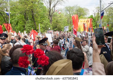 Rostov-na-Donu, RUSSIA - May 9,2017: Immortal Regiment procession in Victory Day- hundreds of people marching toward the Red Square with flags and portraits. Elderly man in the crowd.