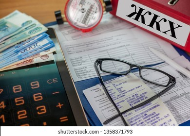 "Rostov-ON Don, Russia- April 02, 2019:Payment of utility bills for electricity and water: receipt, bills and a calculator. On the folder abbreviation Russian letters ""housing and communal services"""
