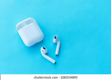 ROSTOV-ON-DON, RUSSIA - APRIL 28, 2018: Apple AirPods wireless Bluetooth headphones and charging case for  Apple iPhone on a blue background. New Apple Earpods Airpods and box.