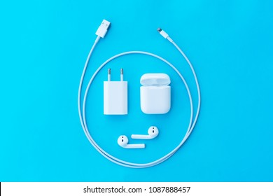 ROSTOV-ON-DON, RUSSIA - APRIL 28, 2018: Top view plastic  wireless Apple AirPods, charging case, Lighning USB, adapter on a pastel blue background for  Apple iPhone. New Apple Earpods Airpods in box.