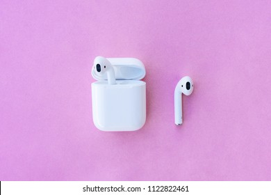 ROSTOV-ON-DON, RUSSIA - APRIL 28, 2018: Apple AirPods wireless Bluetooth headphones and charging case for  Apple iPhone. New Apple Earpods Airpods in box on a pink background