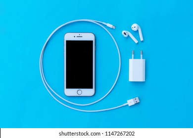 ROSTOV-ON-DON, RUSSIA - APRIL 28, 2018: Top view plastic white wireless Apple AirPods, charging case, smartphone iphone 8, iphone 7, iphone 6, Lighning USB, adapter on a pastel blue background for  Ap