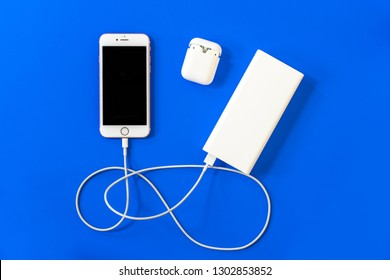 ROSTOV-ON-DON, RUSSIA - APRIL 28, 2018: Top view  white wireless Apple AirPods, charging, power bank, smartphone iphone 8, iphone 7, iphone 6, Lighning USB, adapter on a pastel blue background