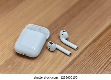 Rostov-on-Don, Russia - Dec. 2018: Apple airpods on wooden blurred background. Apple wireless earphones with charger box, chosen focus. Indoors, copy space, close up.
