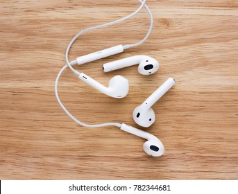 Rostov-on-Don, Russia - December 12, 2017: Airpods and Earpods are lying on a wooden surface. Two pairs of headphones from apple on a wooden table.