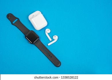 ROSTOV-ON-DON, RUSSIA - February 24, 2019: Apple Watch Series 4 and AirPods wireless Bluetooth headphones and charging case for  Apple iPhone on blue background.