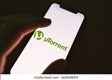 Rostov-on-Don / RUSSIA - January 19 2020: smartphone with μTorrent logo on the screen. hand touching the screen