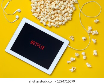 Rostov-on-Don, Russia January 25, 2019: a yellow table with scattered popcorn and the Netflix logo on the Apple iPad and headphones. View from above.
