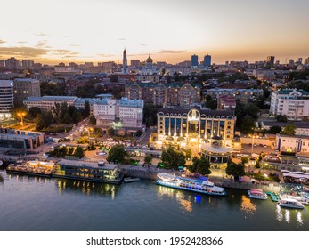 Rostov-on-Don, Russia - July 06, 2020: aerial view of the Don River and embankment at sunset. Bridges, buildings, light of lanterns is reflected in water.