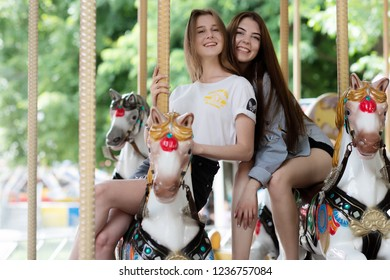 Rostov-on-don, Russia ,July 20 , 2018: two girlfriend girls in the Park on carousel rides .happy women riding carousel horses equipment in the popular amusement park and showing victor hands gestures