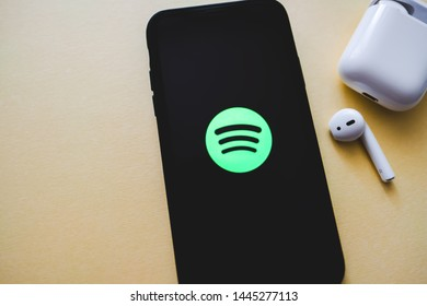 ROSTOV-ON-DON / RUSSIA - July 8 2019: Screen shot of Spotify app showing on iPhone X with AirPods on yellow background. Spotify is music streaming service
