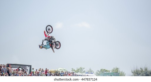 "Rostov-on-Don, Russia- June 05,2016: The athlete performs a jump on a motorcycle in the competition of tractors called ""Bison Track Show"""