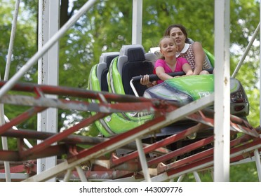 """Rostov-on-Don, Russia- June 13: Girl with mum ride attraction """"Rollercoaster"""""""