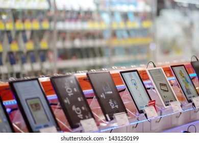 Rostov-on-Don , Russia , June 22, 2019: New smartphones and tablets on a white showcase with antitheft system in electronic store